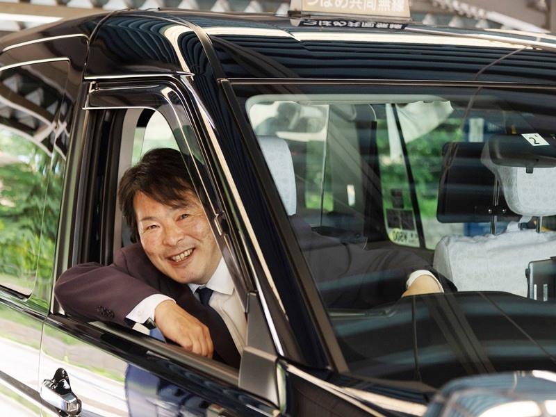 笑顔で車から顔を出すドライバー